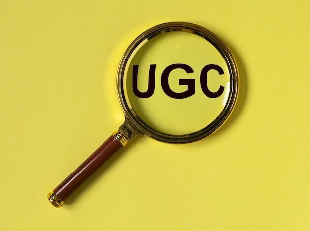 루페가있는 노란색 배경에 소셜 미디어의 ugs 또는 사용자 생성 콘텐츠 약어입니다.