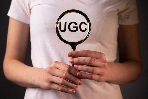 여성의 손에있는 확대경을 통한 소셜 미디어의 ugs 또는 사용자 생성 콘텐츠 약어입니다.