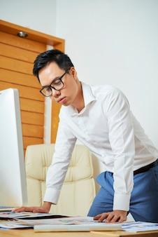 完璧なモバイルアプリケーションのレイアウトに取り組んでいるときに彼のオフィスの机に寄りかかってuiデザイナー