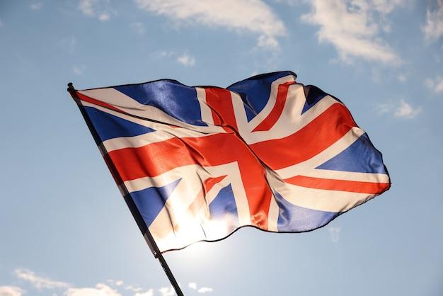 영국 국기가 바람에 날리고 흔들며 일몰 전 황금 시간에 백라이트, 흐린 푸른 하늘, 영국 애국심의 상징, 낮은 각도, 측면 전망