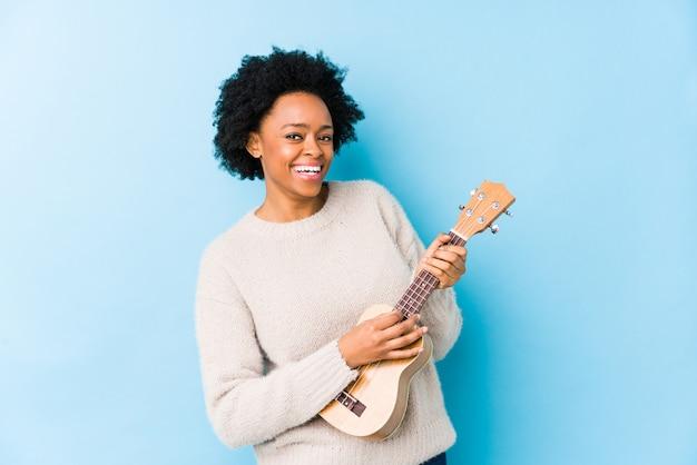 Молодая афро-американская женщина играя ukelele