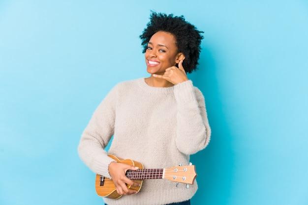 Молодая афро-американская женщина играя ukelele изолировала показывать жест звонка мобильного телефона с пальцами.