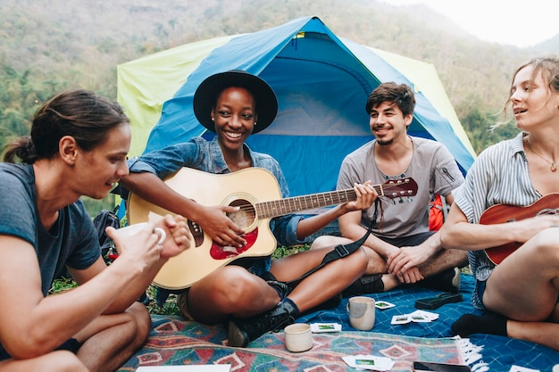 キャンプ場で若い大人の友人のグループは、ギターとukeleleを再生し、一緒に歌う