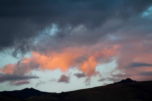 アルタイukok曇りの寒さで山に沈む夕日。野生の遠隔地、誰もいない。山の上の雨の雲