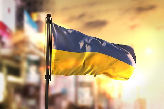 Флаг украины против города размытый фон при восходе солнца
