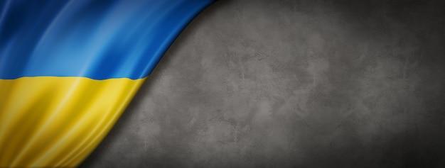 Ukraine flag on concrete wall. horizontal panoramic banner. 3d illustration
