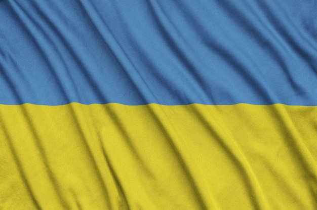 Ukraine flag  is depicted on a sports cloth fabric with many folds.