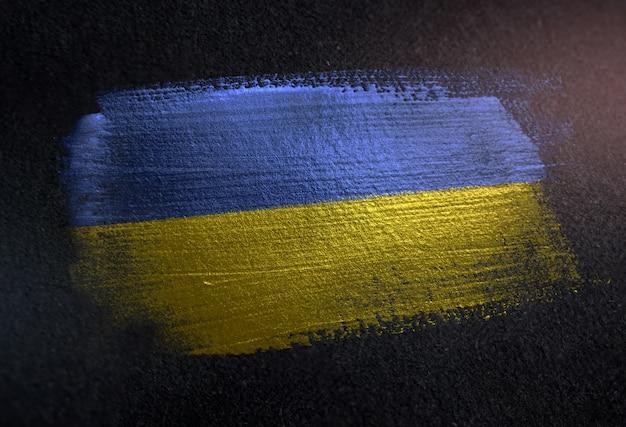 Ukraine flag made of metallic brush paint on grunge dark wall