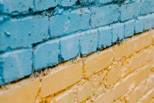 Флаг украины нарисован на старой кирпичной стене, фоне желто-голубой кирпичной стены.