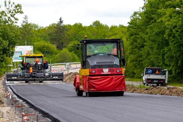 ウクライナ、khmelnytsky地域、krasyliv。 2021年5月。アスファルト敷設中の道路上のアスファルトペーバーとローラー。道路の修理