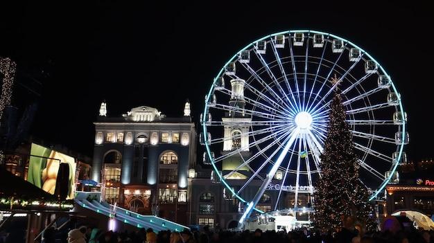 Украина, киев - 15 января 2019 года. освещенное колесо обозрения на контрактовой площади в киеве вечером.