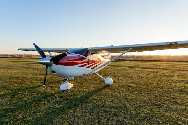 Ukraine kiev october 11, 2018: a small aircraft of white and red colors standing on the airfield on the green grass on the background of the sky.