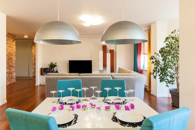 ウクライナキエフ2017年10月29日:テレビ付きのソファの背景にberyuzovymiの椅子が付いたアパートの白いテーブルを提供しました。アパートのテーブルを提供しました。