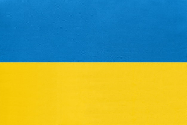 Ukraine national fabric flag, textile background. symbol of international world european country.