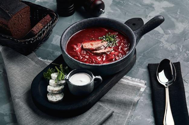 Украинский и русский традиционный свекольный суп - борщ в миску с реберным мясом, ржаным хлебом, кусочками бекона и сметаной на деревянном фоне.