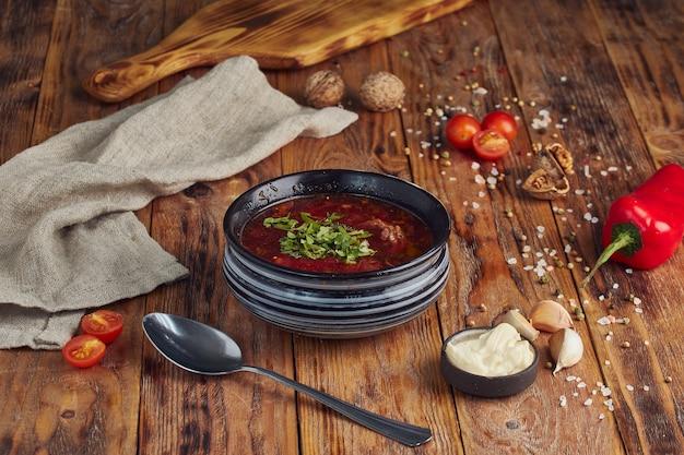 Украинский и русский традиционный свекольный суп или борщ в миске с мясом на деревянном столе