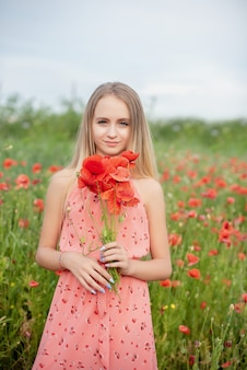 Ukrainian beautiful girl in field of poppies and wheat.