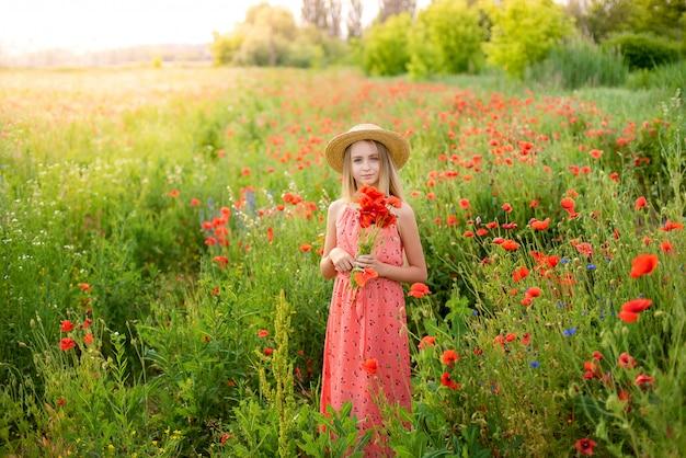 Ukrainian beautiful girl in field of poppies and wheat.