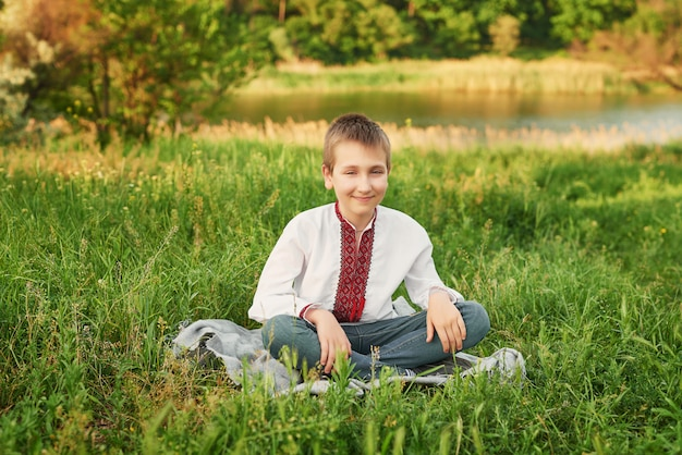 Ukrainian child boy in embroidery on the field