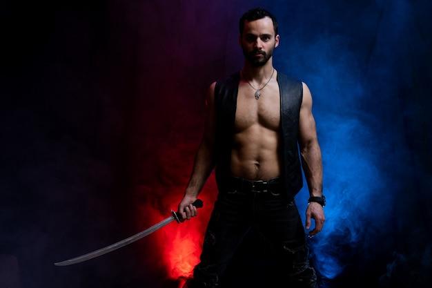 黒とスモークの背景に分離された長い剣でポーズをとるウクライナのコサック