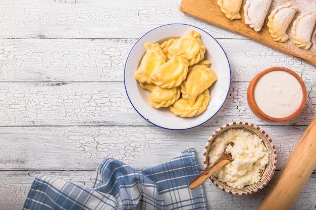 Украинские пельмени, вареники или пироги, вареники, вареники, подаются с творогом на борту. национальная русская кухня, натуральный органический домашний хлебобулочный продукт, вид сверху.