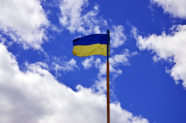 Ukrainian flag against the blue sky with clouds