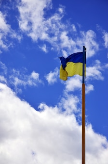 Ukrainian flag against the blue sky with clouds.