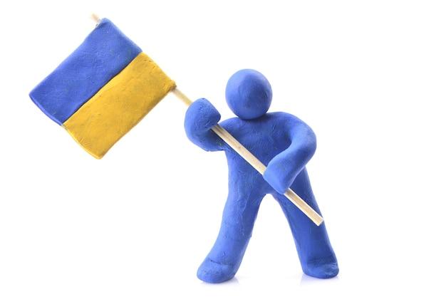 Украинский флаг в руках куклы из голубой глины, изолированной на белом фоне