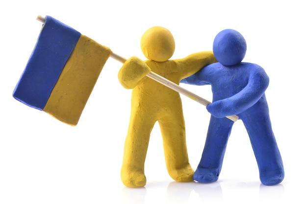Украинский флаг держат куклы человека из желтой и голубой глины, изолированные на белом фоне