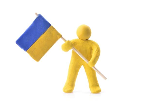 Украинский флаг в руках куклы из желтой глины, изолированной на белом фоне