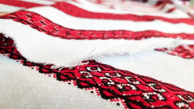 ウクライナの民謡の手刺繡。白い布に赤黒の糸で刺された飾り。黒と赤の糸で刺された飾り。白い布に民族のウクライナの民謡の刺繡。