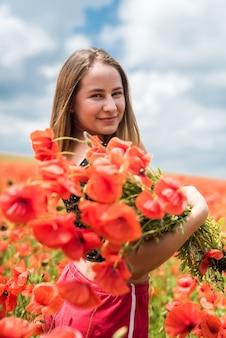 フィールド、夏の時間でポピーの花束を保持しているスポーツウェアのウクライナの女の子