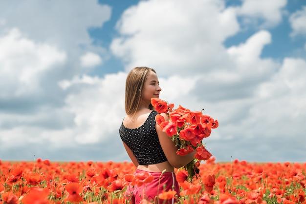 필드, 여름 시간에 양 귀 비의 꽃다발을 들고 sportwear에 우크라이나어 소녀
