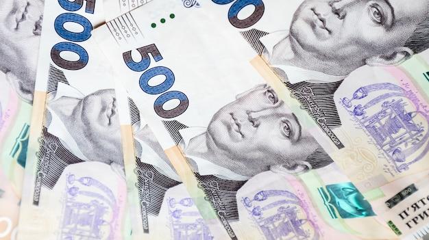 Украинская гривна, множество новых купюр достоинством в 500 гривен красиво разложены на столе. финансовый фон, деньги.