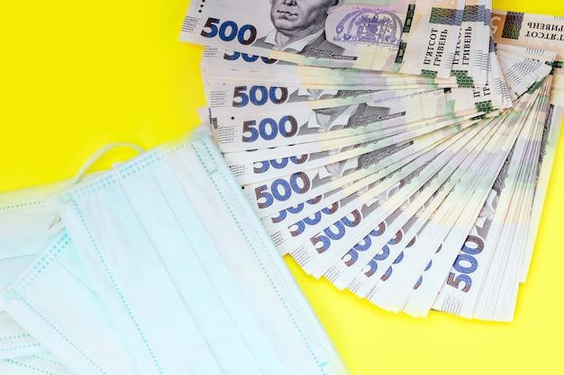 Украинская гривна деньги с медицинской защитной маской, концепция.