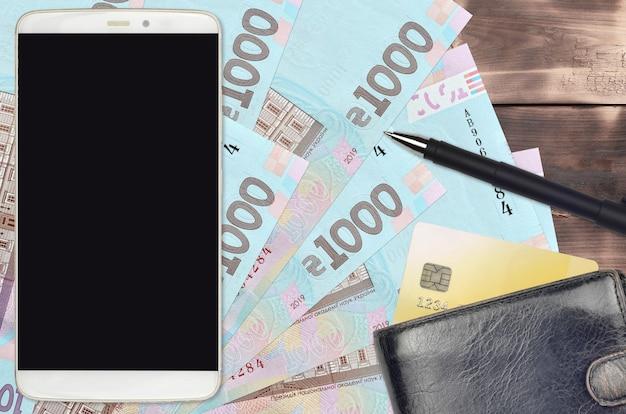 Украинские гривны и смартфон с кошельком и кредитной картой