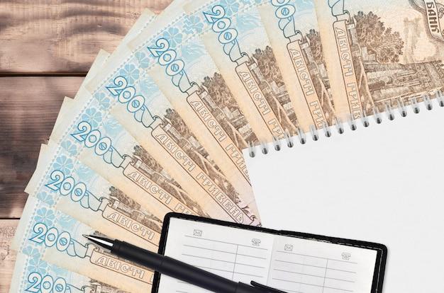 Поклонник банкнот украинской гривны и блокнот с записной книжкой и черной ручкой