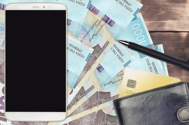 Ukrainian hryvnias bills and smartphone with purse and credit card