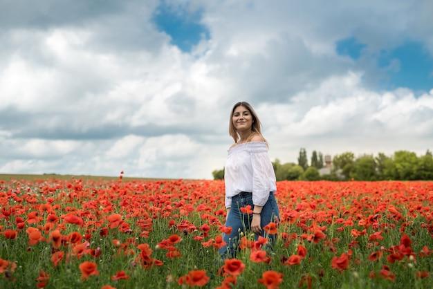 ポピー畑を歩くウクライナの女性、官能性、ライフスタイルの概念