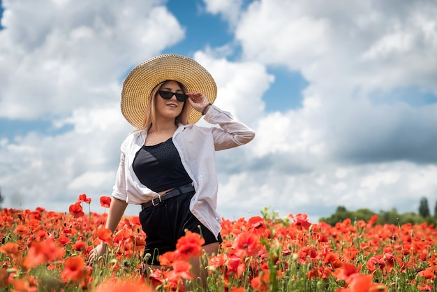 양 귀 비 필드를 따라 걷는 우크라이나 여자