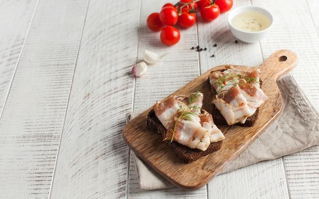 Украинское сало из свинины, посыпанное свежей рубленой зеленью на деревянной доске