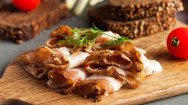 Украинское сало из свинины, посыпанное свежей рубленой зеленью на деревянной доске Premium Фотографии