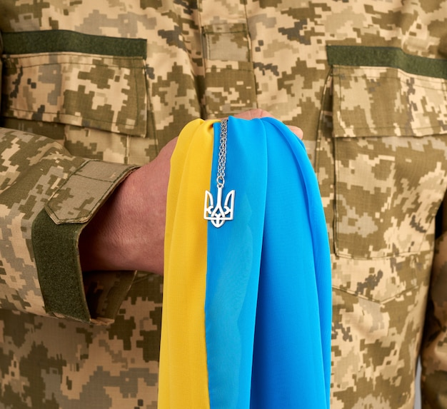Ukrainian man warrior dressed in a military pixel uniform holds the yellow-blue flag of the state of ukraine and on the chain a small coat of arms of the country of trident