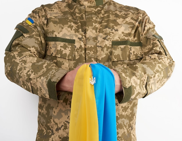 Ukrainian man warrior dressed in a military pixel uniform holds the yellow-blue flag of the state of ukraine