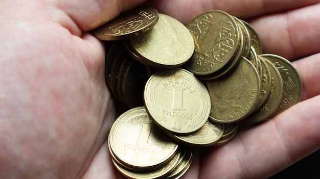 Украинские металлические монеты номиналом 1 гривна на ладони мужской руки. горсть или куча монет в руках. понятие выхода на пенсию, сбережений и богатства, кредита и ипотеки, бедности.