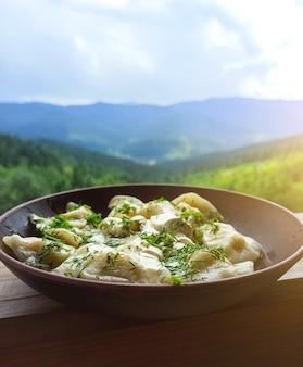 Украинская национальная еда в горах. вареники в тарелке на открытом воздухе. питание в летнее время.