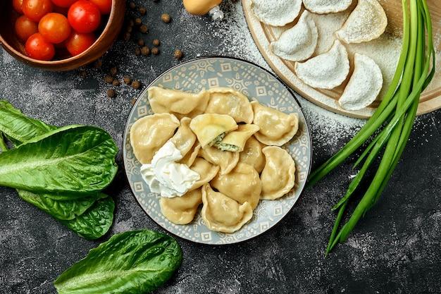 우크라이나 또는 폴란드 전통 요리-피에로 기 또는 바레 니키 (만두)에 시금치와 치즈, 사워 크림을 어두운 테이블 위에 올려 놓습니다. 클로즈업, 선택적 초점