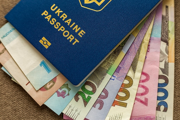 Ukrainian passport and money, ukrainian hryvna banknotes bills on copy space, top view. traveling and  finance problems concept.