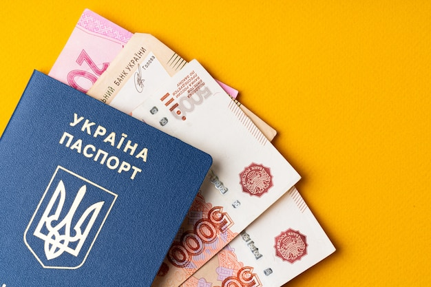 Ukrainian passport with ukrainian currency hryvnia and russian roubles inside