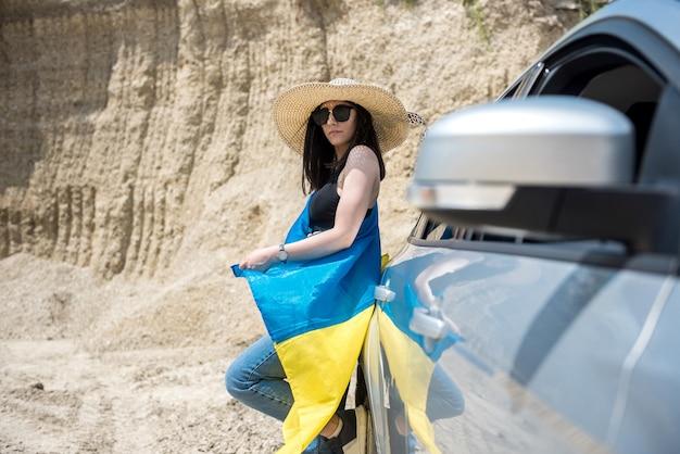 차 근처 모래 채석장에서 포즈를 취하는 국기와 우크라이나어 예쁜 여자